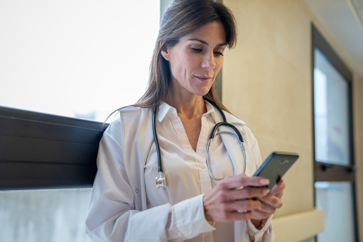 female doctor at a hospital tweeting on her smartphone