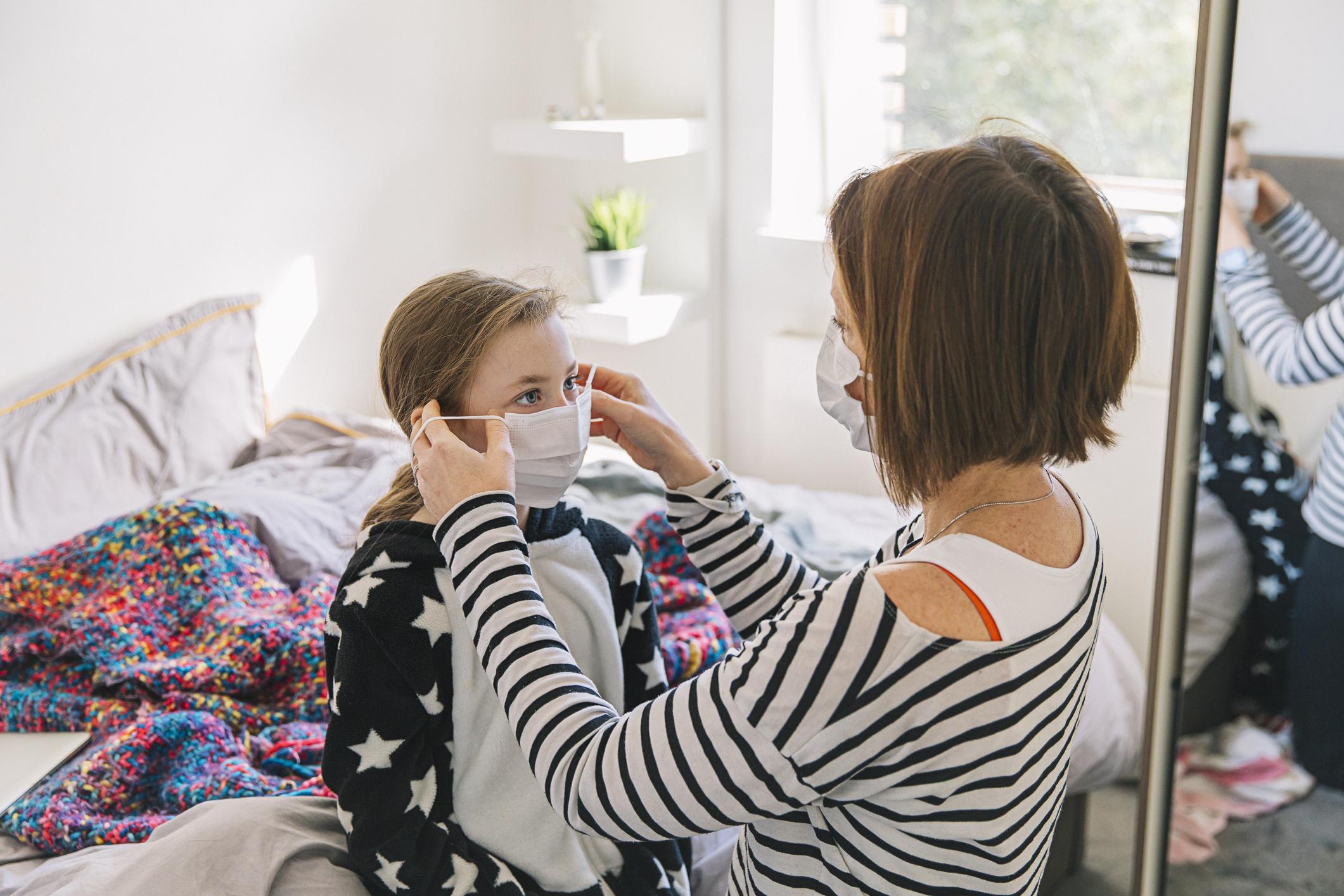 Woman puts mask on child
