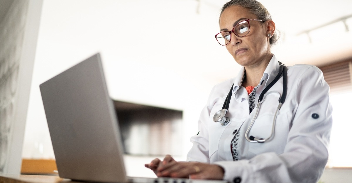 Physician writing referral on laptop