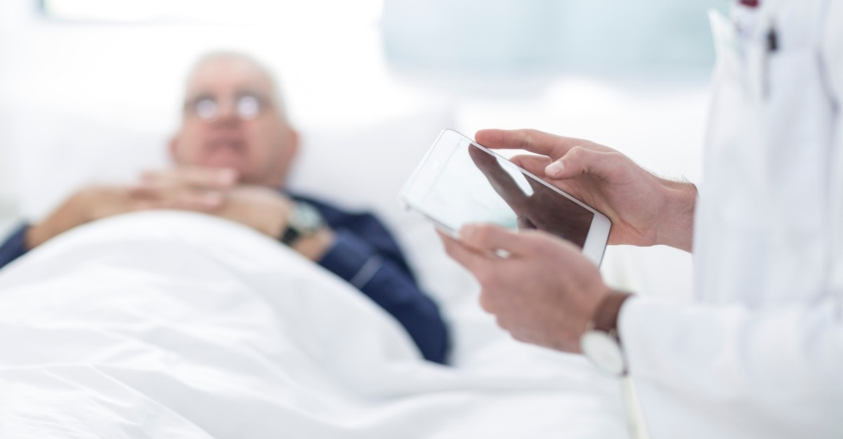 Close-up of doctor using a digital tablet next to patient