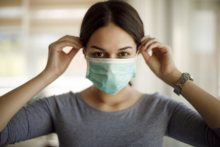 young woman putting on a protective mask