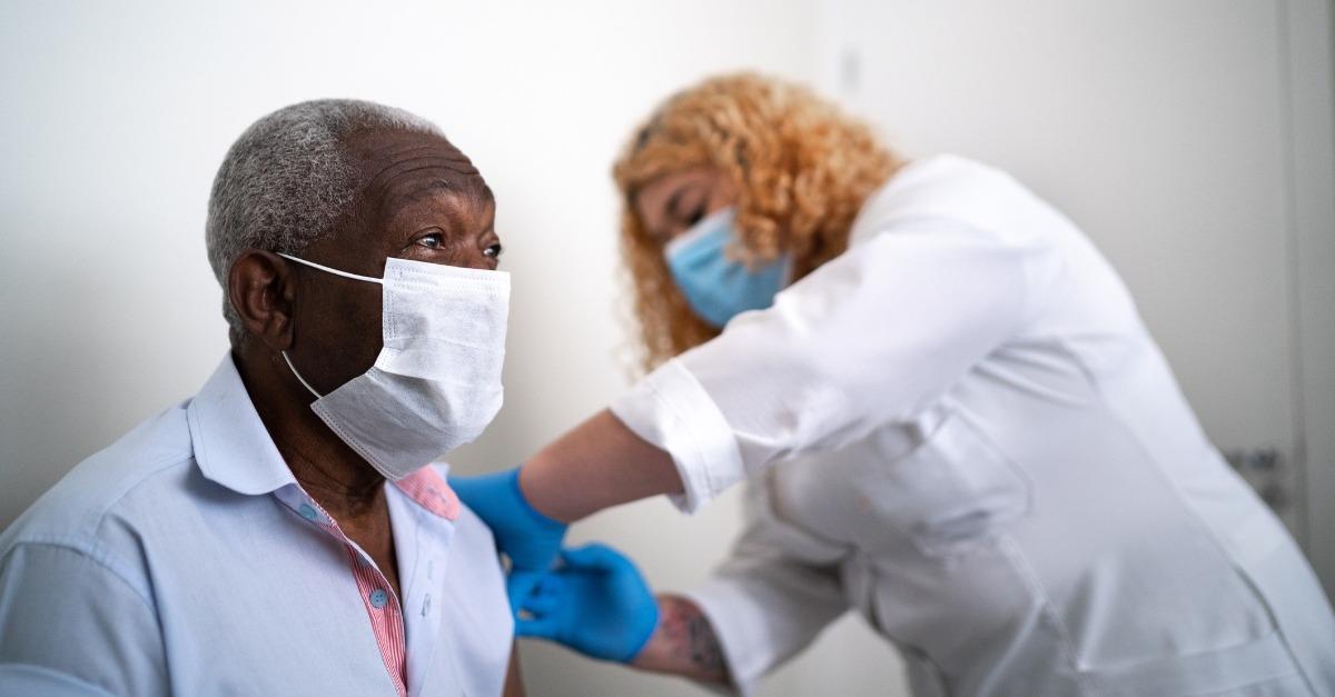 Nurse applying viral vector vaccine on patient's arm